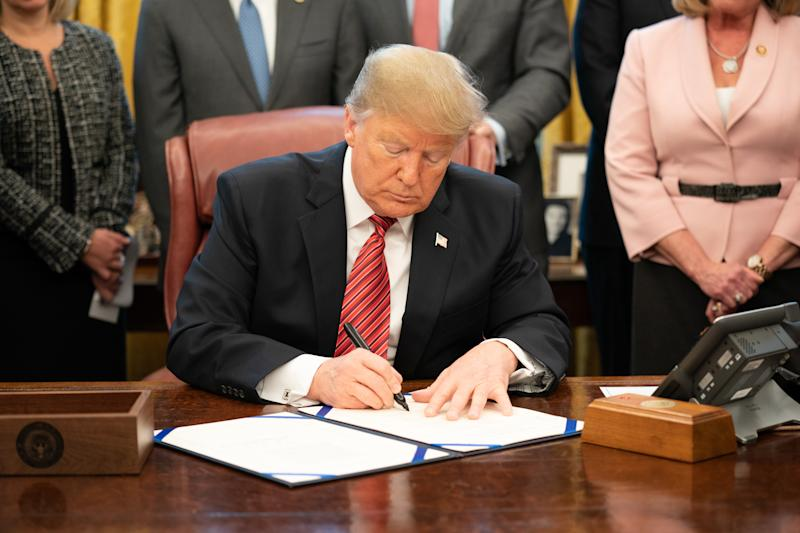 Cory Gardner President Trump signing a bill at his desk in the Oval Office.