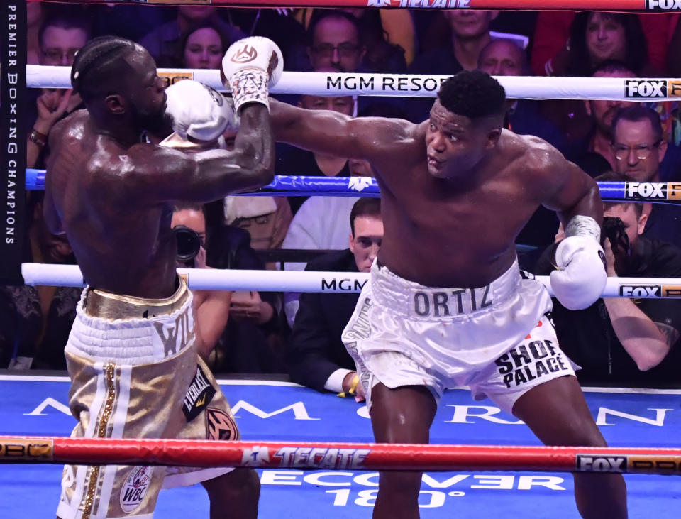 LAS VEGAS, NV - NOVEMBER 23:  (in White/Gold trunks) Deontay Wilder goes 7 rounds with Luis Ortiz at MGM Grand Garden Arena on November 23, 2019 in Las Vegas, United States.  Deontay Wilder took the win by KO Luis Ortiz in the 7th round.   (Photo by MB Media/Getty Images)