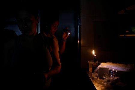 Women work at the kitchen of a restaurant during a blackout in Caracas, Venezuela March 27, 2019. REUTERS/Carlos Garcia Rawlins
