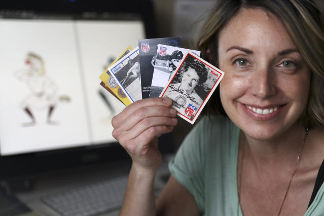 """In this April 30, 2020, photo, Anika Orrock holds some of her autographed baseball cards of players from the All-American Girls Baseball League at her home in Nashville, Tenn. Orrock has written and illustrated a book on the players titled """"The Incredible Women of the All-American Girls Professional Baseball League."""" (AP Photo/Mark Humphrey)"""