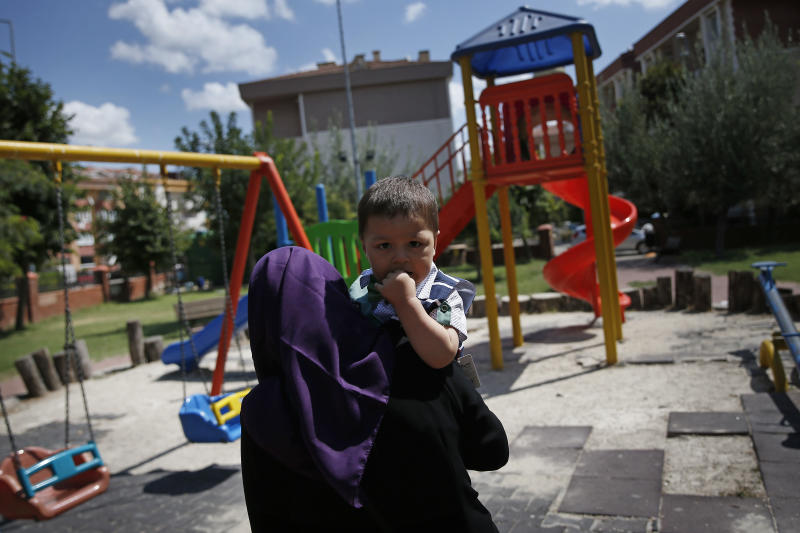 In this Aug. 21, 2018, photo, Meripet, 29, carries her son Abduweli, at a playground in Istanbul, Turkey. Meripet came to Turkey in February 2017 to visit her sick father, leaving four children behind. While in Turkey, she heard Uighur passports were being seized and that people who had gone abroad were being taken to reeducation – so she stayed in Turkey, giving birth to Abduweli. She hasn't seen her other four children since, and heard they were taken to a live-in kindergarten in Hotan, China. (AP Photo/Lefteris Pitarakis)
