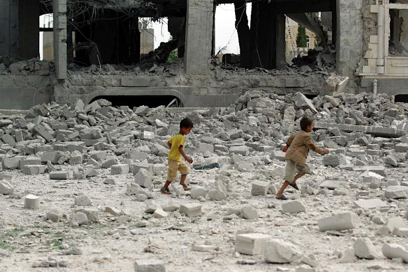 Yemeni children run amidst the debris of a house, said to belong to a Huthi leader, destroyed in an air-strike by the Saudi-led coalition in Sanaa on May 29, 2015 (AFP Photo/Mohammed Huwais)