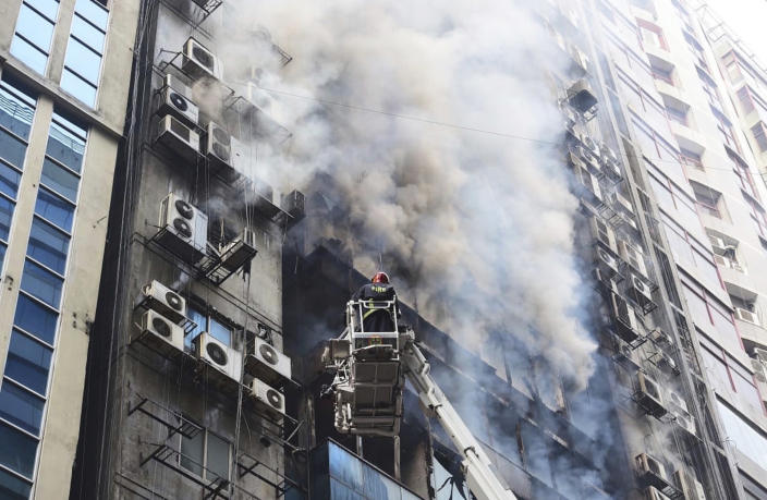 FILE - In this March 28, 2019, file photo, a firefighter works to douse a fire in a multi-storied office building in Dhaka, Bangladesh. The fire in Banani, a busy upscale commercial district, exposed the vulnerabilities hidden behind the glass towers that have become symbols of Bangladesh's rapid growth. While Bangladesh's economy has expanded by more than 6 percent annually in the last decade, safety regulations and enforcement have lagged behind, experts say. (AP Photo/Mahmud Hossain Opu, File)