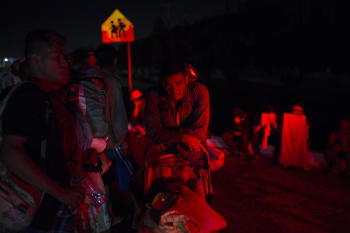 A family waits in hope of a ride among other Central American migrants participating in a caravan that is slowly making its way toward the U.S. border, outside Arriaga, Mexico, before dawn on Saturday, Oct. 27, 2018. Many migrants said they felt safer traveling and sleeping with several thousand strangers in unknown towns than hiring a smuggler or trying to make the trip alone. (AP Photo/Rodrigo Abd)