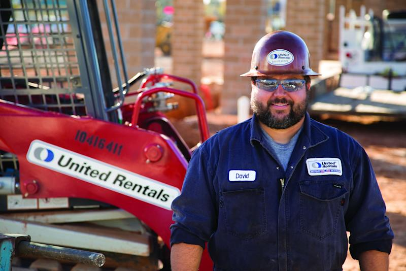 Person wearing hard hat next to a piece of equipment with United Rentals logo on it.