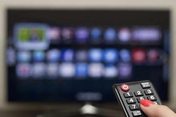 A woman controls a smart TV with a remote.