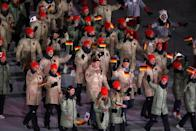 <p>German athletes emerge for the parade wearing khaki-color puffer jackets, black pants, and crimson beanies during the opening ceremony of the 2018 PyeongChang Games. (Photo: Sean M. Haffey/Getty Images) </p>