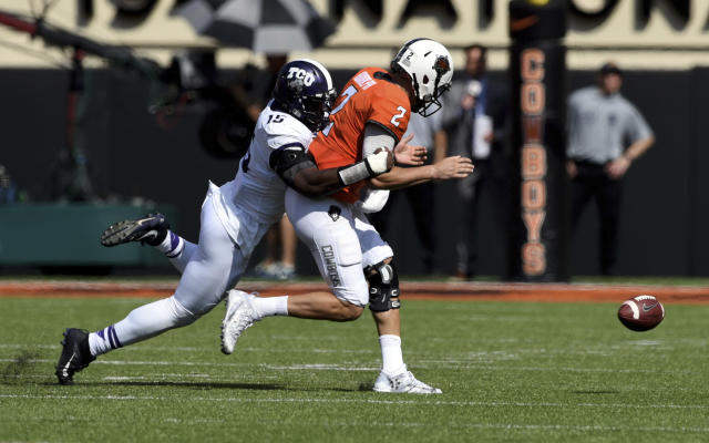 "TCU defensive end Ben Banogu, left, forces a fumble by Oklahoma State quarterback <a class=""link rapid-noclick-resp"" href=""/ncaaf/players/239330/"" data-ylk=""slk:Mason Rudolph"">Mason Rudolph</a>, during the first half of an NCAA college football game in Stillwater, Okla., Saturday, Sept. 23, 2017.(AP Photo/Brody Schmidt)"