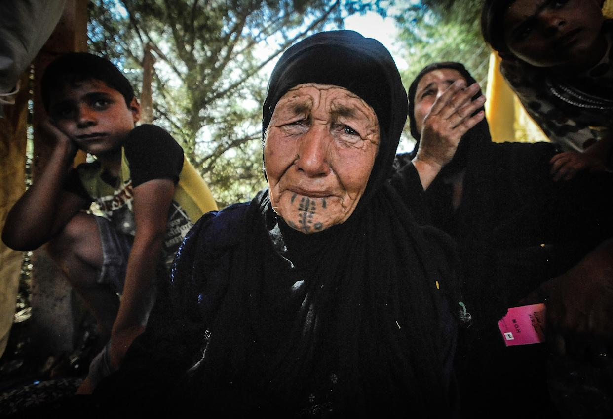 An 80 year old women becomes overwhelmed by the trauma of walking for 2 days from Qaraqosh is waiting to receive medical attention, in Irbil, Iraq, on August 10, 2014.
