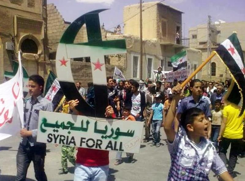 In this citizen journalism image provided by Sham News Network SNN, an anti-Syrian regime protester, holds up a Cross and Crescent painted with colors of the Syrian revolution flag during a demonstration against Syrian President Bashar Assad, at the Damascus suburb of Yabroud, Syria, Friday, May 18, 2012. Syrian security forces fired tear gas and live ammunition to disperse thousands rallying Friday in Aleppo in what activists said was the largest protest yet in a city that has largely remained loyal to President Bashar Assad during the country's 15-month uprising. (AP Photo/Sham News Network, SNN)THE ASSOCIATED PRESS IS UNABLE TO INDEPENDENTLY VERIFY THE AUTHENTICITY, CONTENT, LOCATION OR DATE OF THIS HANDOUT PHOTO