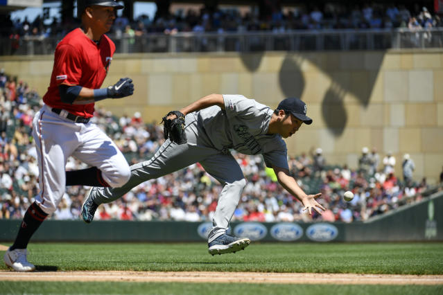 Seattle Mariners pitcher Yusei Kikuchi, right, is too late with the throw to first as Minnesota Twins' Ehire Adrianza, left, runs the baseline after bunting in the second inning of a game Thursday, June 13, 2019, in Minneapolis. (AP Photo/Craig Lassig)