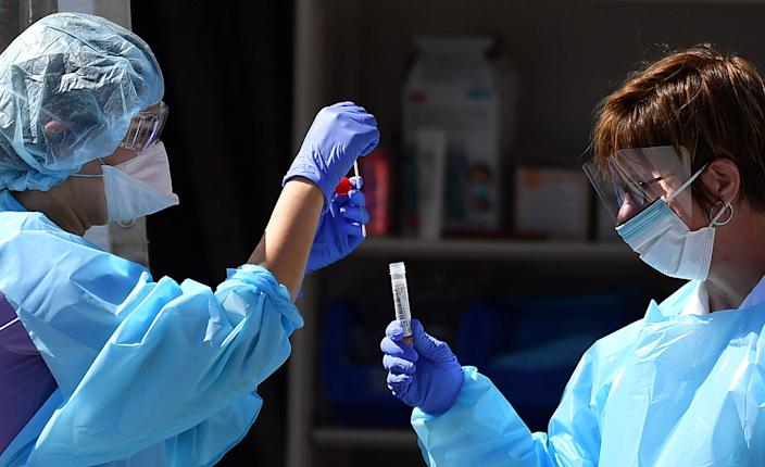 Medical workers at Kaiser Permanente French Campus test a patient for the novel coronavirus, COVID-19, at a drive-thru testing facility in San Francisco, California on March 12, 2020. (Photo by JOSH EDELSON/AFP via Getty Images)