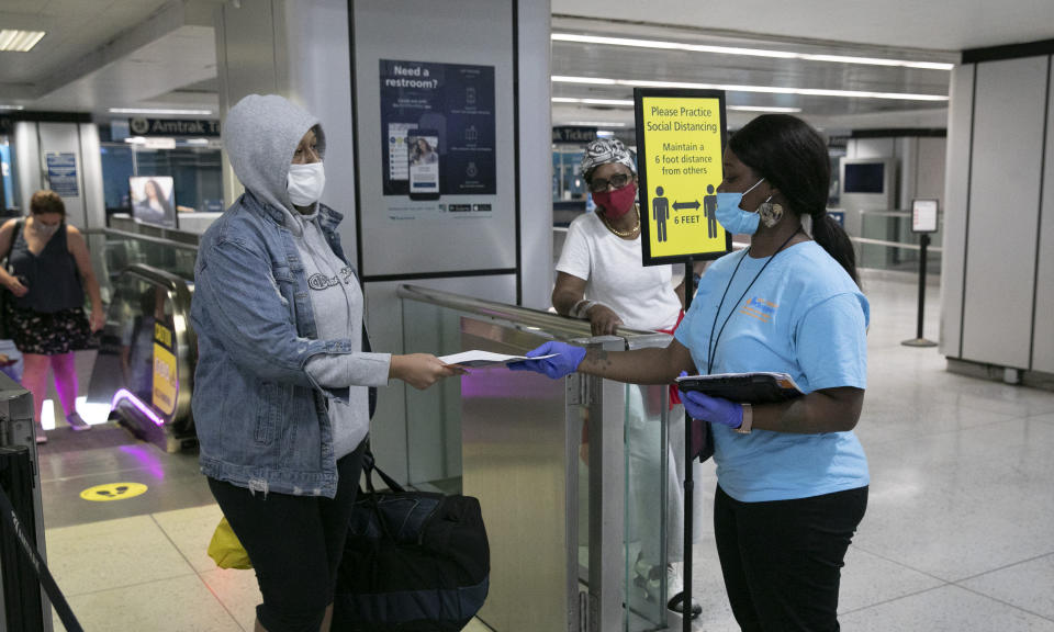Shaquanna Parnell, right, with the Mayor's Office of Public Engagement, hands an information leaflet to a passenger arriving at Amtrak's Penn Station, Thursday, Aug. 6, 2020, in New York. Mayor de Blasio is asking travelers from 34 states and Puerto Rico, where COVID-19 infection rates are high, to quarantine for 14 days after arriving in the city. (AP Photo/Mark Lennihan)
