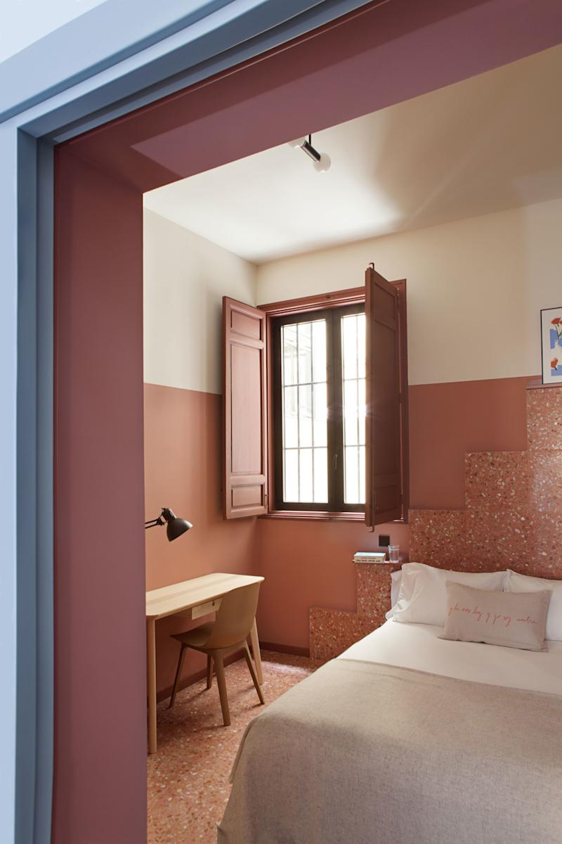 """After: The terrazzo installation in the clay-colored """"Earth Room"""" isn't just for visual interest, although it definitely succeeds there. It also serves as headboard and bookshelf, leaving plenty of room for a work space, a must for any student."""