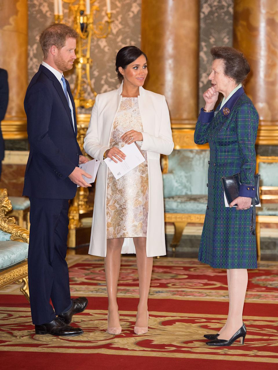 Britain's Prince Harry, Duke of Sussex, (L) and Britain's Meghan, Duchess of Sussex (C) and Britain's Princess Anne, Princess Royal, (R) attend a reception to mark the 50th Anniversary of the investiture of The Prince of Wales at Buckingham Palace in London on March 5, 2019. - The Queen hosted a reception to mark the Fiftieth Anniversary of the investiture of Britain's Prince Charles, her son, as the Prince of Wales. Prince Charles was created The Prince of Wales aged 9 on July 26th 1958 and was formally invested with the title by Her Majesty The Queen on July 1st 1969 at Caernarfon Castle. (Photo by Dominic Lipinski / POOL / AFP)        (Photo credit should read DOMINIC LIPINSKI/AFP via Getty Images)