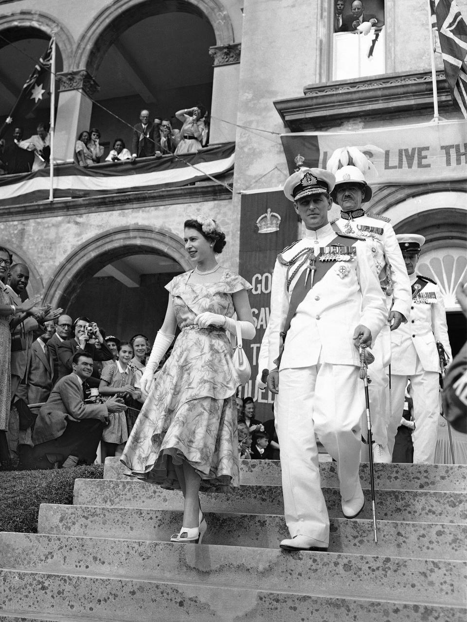 FILE - In this file photo dated Nov. 25, 1953, Britain's Queen Elizabeth II and the Duke of Edinburgh leaving the House Of Assembly after the Queen had addressed Bermuda's Colonial Parliament, in Hamilton, Bermuda. The Governor of Bermuda Lieutenant General Sir Alexander Hood follows the Queen and Duke down the steps. Prince Philip who died Friday April 9, 2021, aged 99, lived through a tumultuous century of war and upheavals, but he helped forge a period of stability for the British monarchy under his wife, Queen Elizabeth II. Philip helped create the Commonwealth of nations, with the queen at its head, in an attempt to bind Britain and its former colonies together on a more equal footing. (AP Photo, FILE)