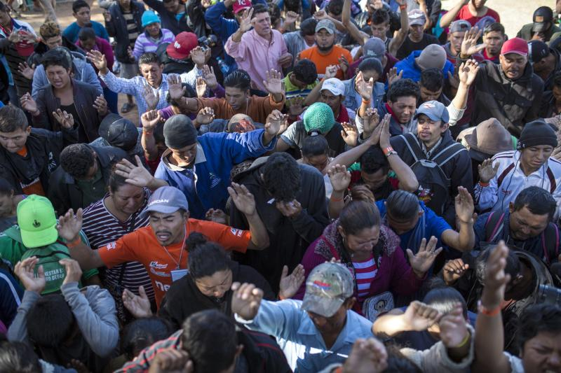 Central American migrants, part of the caravan hoping to reach the U.S. border, pray at a temporary shelter in Tijuana, Mexico, Friday, Nov. 16, 2018. As thousands of migrants of asylum-seekers converge on the doorstep of the United States, what they won't find are armed American soldiers standing guard, that's because U.S. military troops are prohibited from carrying out law enforcement duties. (AP Photo/Rodrigo Abd)