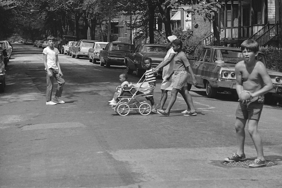 Division of opinions in Chicago. White children play ball in street just west of Ashland as an African American  family passes. White homeowners to west of Ashland have formed block clubs, designed to keep the neighborhood white. (AP Photo/JLP)
