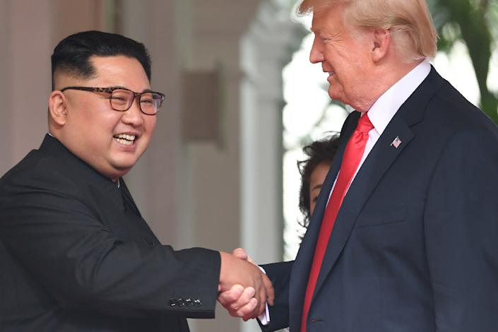 Trump and Kim shake hands.