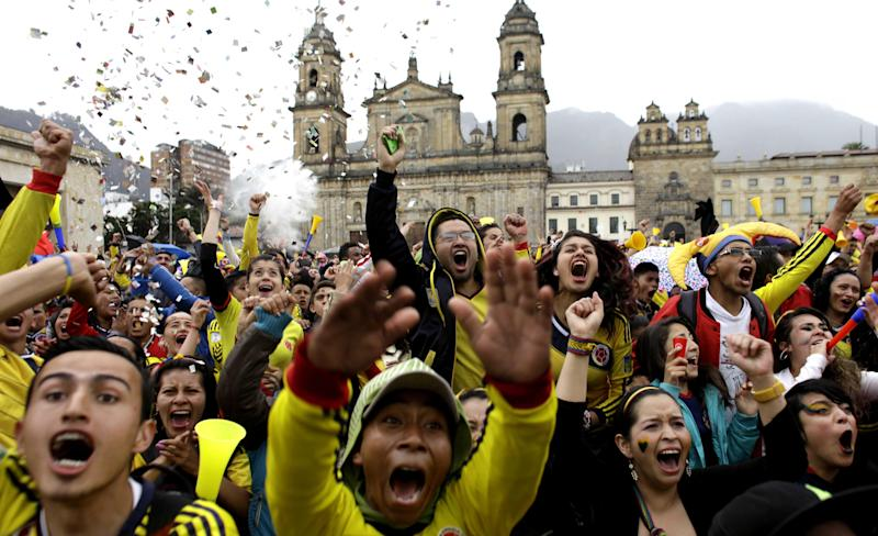 Colombia soccer fans celebrate after their team's World Cup victory over Japan in Bogota, Colombia, Tuesday, June 24, 2014. Substitute James Rodriguez scored a brilliant goal and set up two more for Jackson Martinez as Colombia beat Japan 4-1 on Tuesday to confirm top spot in Group C and eliminate the Asian champions from the World Cup