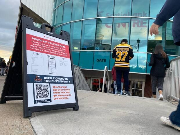 Fans enter Scotiabank Centre in downtown Halifax on Oct. 2, passing a sign outlining the requirement to show proof of vaccination against COVID-19. (Submitted by Nick McDow - image credit)