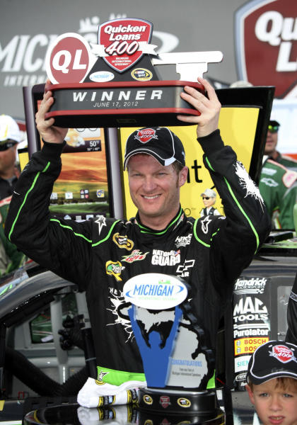 Dale Earnhardt Jr. lifts the trophy after winning the NASCAR Sprint Cup Series Quicken Loans 400 auto race at Michigan International Speedway, Sunday, June 17, 2012, in Brooklyn, Mich. (AP Photo/Bob Brodbeck)