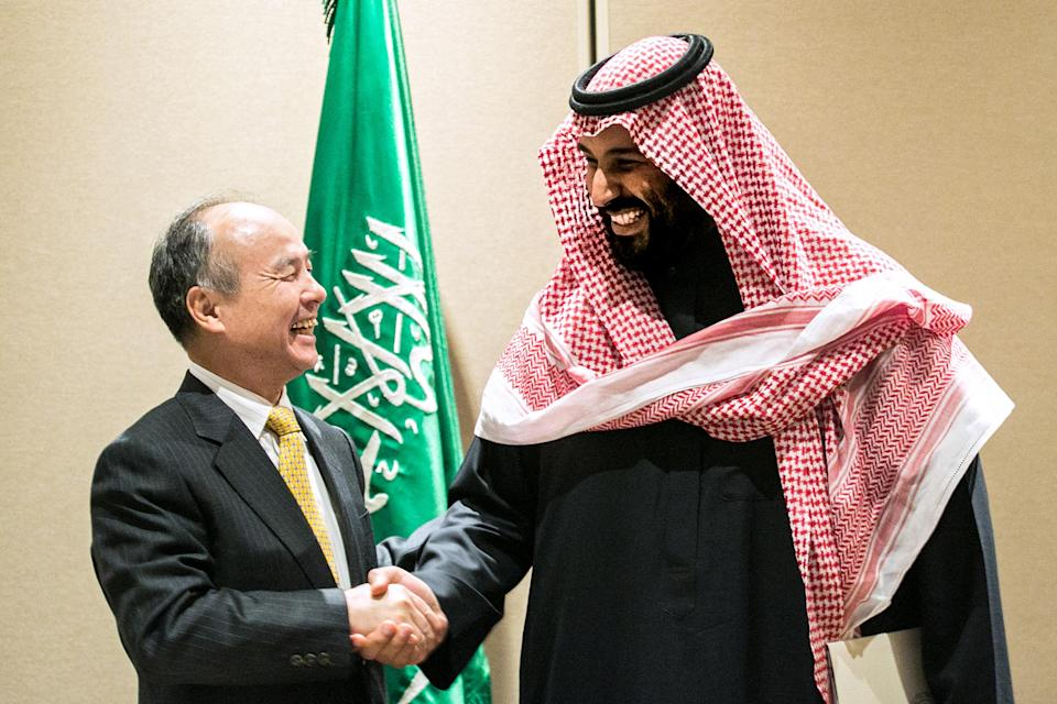 Son, left, shakes hands with Mohammed bin Salman, Saudi Arabia's crown prince, after signing an agreement in New York, U.S., on Tuesday, March 27, 2018. (Jeenah Moon/Bloomberg via Getty Images)