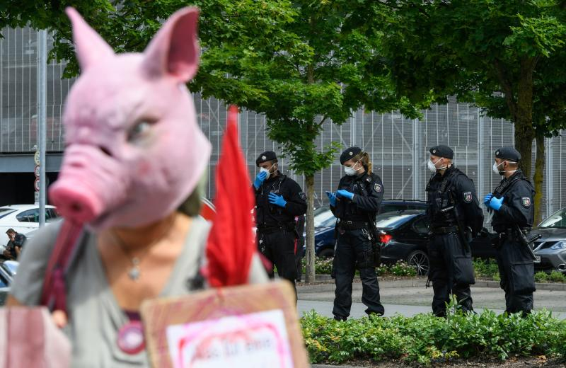 A demonstrator wearing a pig mask protests in front of the headquarters of abattoir company Toennies in Rheda-Wiedenbrueck, western Germany, on June 20, 2020, where the German army helps to establish a test center for the novel coronavirus. - The company stopped its production after hundreds of employees were tested positive on the novel coronavirus.