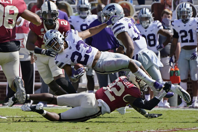 Kansas State wide receiver Joshua Youngblood (23) is upended by Oklahoma defensive back Delarrin Turner-Yell (32) in the first half of an NCAA college football game Saturday, Sept. 26, 2020, in Norman, Okla. (AP Photo/Sue Ogrocki).