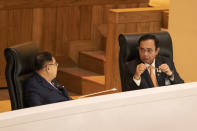 Thailand's Prime Minister Prayuth Chan-ocha, right, listens to Deputy Prime Minister Prawit Wongsuwan before the start of a no-confidence debate at the parliament in Bangkok, Thailand, Tuesday, Feb. 16, 2021. The opposition parties are targeting 10 Cabinet​ ministers with allegations ranging from poor management to corruption. (AP Photo/Sakchai Lalit)