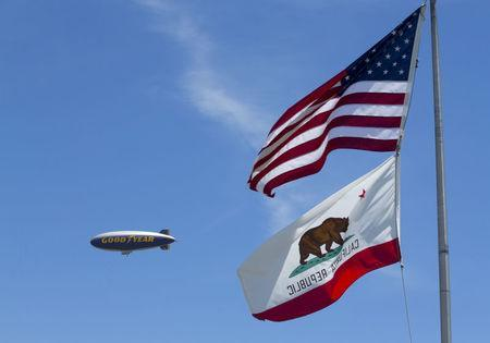 "The Goodyear blimp "" Spirit of America"" flies past the California and U.S. flags in Carson, California August 5, 2015. REUTERS/Mike Blake/File Photo"