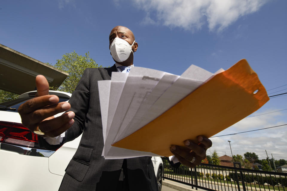 Tennessee State Rep. Harold Love, Jr. talks to the media as he holds a copy of his family's deed to their former house, Monday, July, 19, 2021, on the north side of Nashville, Tenn. Love Jr.'s father, a Nashville city councilman, was forced to sell his family home here to make way for the highway, but put up a fight in the 1960s against the rerouting of Interstate 40 because he believed it would stifle and isolate Nashville's Black community. Love Jr. is now part of a group pushing to build a cap across the highway that creates a community space to help reunify the city. (AP Photo/John Amis)