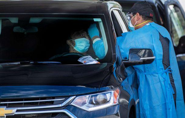 PHOTO: A medical team member administers a COVID-19 test at a drive-through test site in Riverside, Calif., Dec. 9, 2020.  (Los Angeles Times via Getty Images, FILE)