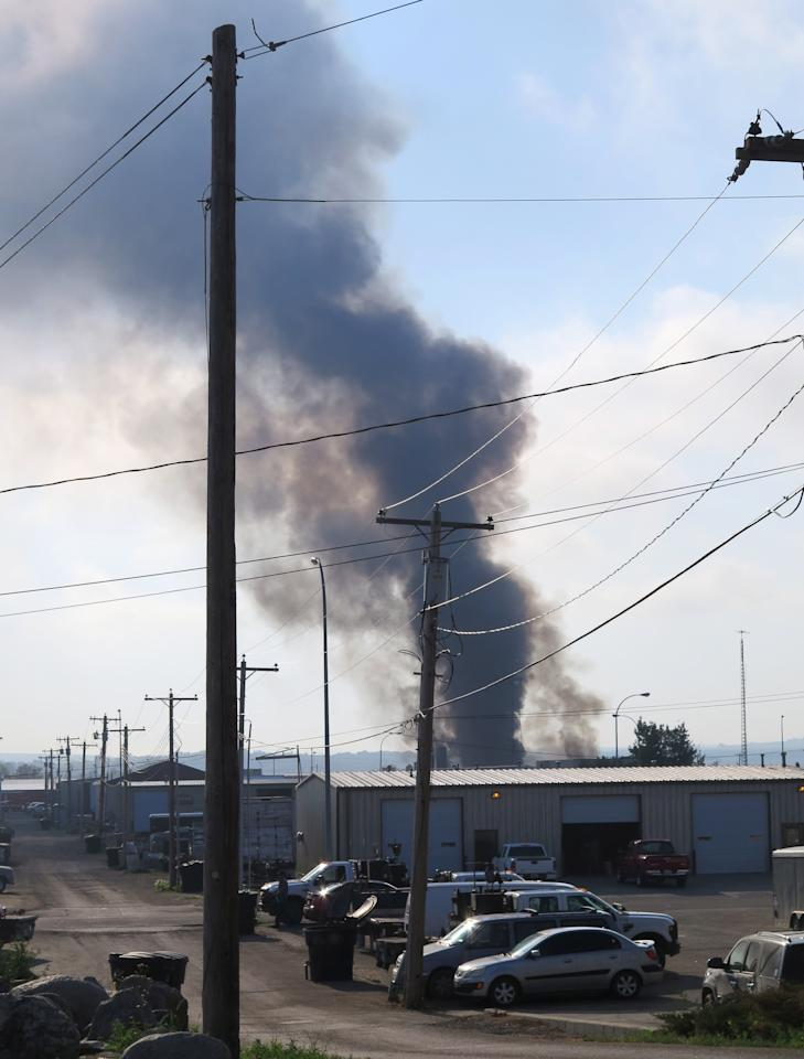 Smoke rises from the site of a fire in an industrial area of Williston, N.D. on Tuesday, July 22, 2014. Authorities have set up an evacuation zone within a half-mile radius of Red River Supply, the site of the fire. No injuries were immediately reported. Red River Supply provides services to oil companies working in North Dakota's oil patch. (AP Photo/Josh Wood)