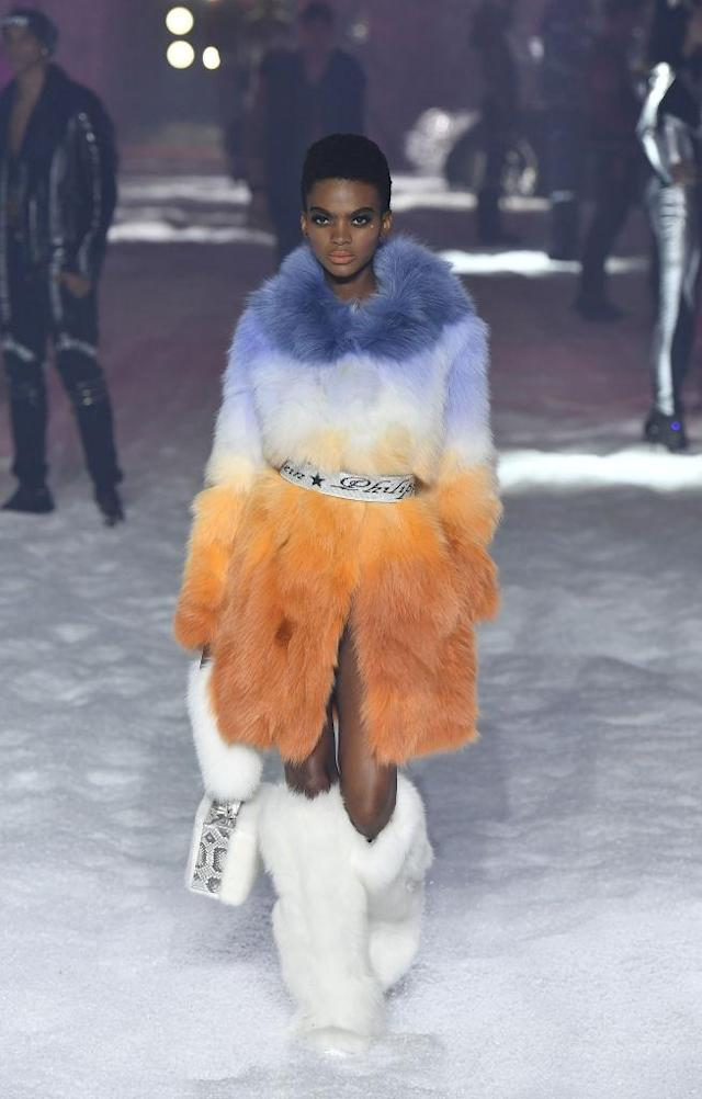 <p>Model wears a blue, orange, and white fur coat and white fur boots at the Philipp Plein FW18 show. (Photo: Getty) </p>