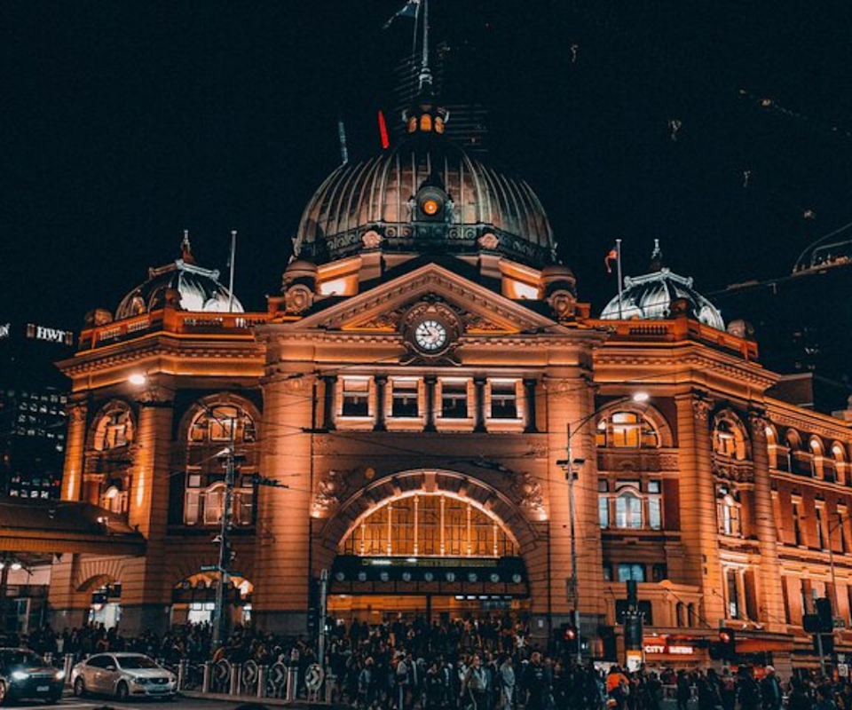 A night time setting of Federation Square train station lit up with lights.
