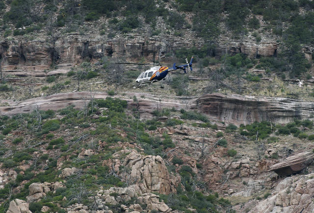 <p>A helicopter flies above the rugged terrain along the banks of the East Verde River during a search and rescue operation for victims of a flash flood on Sunday, July 16, 2017, in Payson, Ariz. (AP Photo/Ralph Freso) </p>
