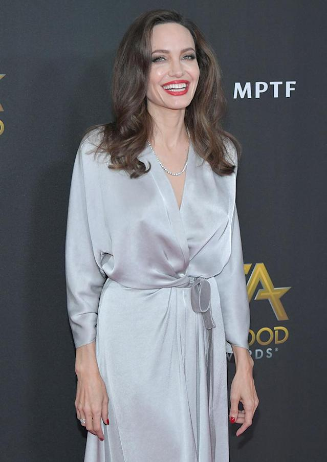 <p>Honoree Angelina Jolie dazzled on the red carpet at the Hollywood Film Awards, wearing a silky silver wrap gown from Jenny Packham's AW17 Catwalk Collection and her famous smile. The supermom was on hand to accept the Hollywood Foreign Language Film Award with Loung Ung for their critically acclaimed film <em>First They Killed My Father</em>. Jolie directed the movie and co-wrote the screenplay with Ung, which is based on Ung's memoir. (Photo: Neilson Barnard/Getty Images) </p>