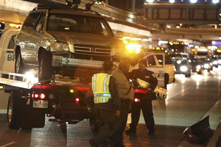 Crews load a vehicle on a truck after it struck a stairwell near Terminal 5 at Los Angeles International Airport