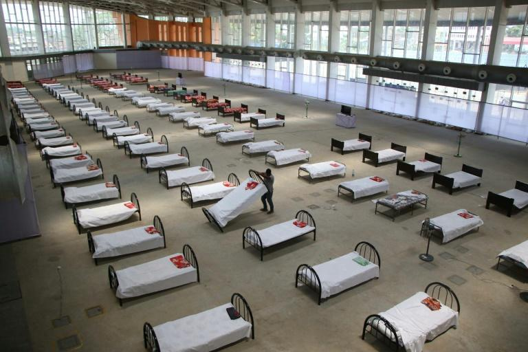 A worker arranges beds at quarantine centre set up in the Hapania International Fair Complex on the outskirts of Agartala, India (AFP Photo/Papri BHATTACHARJEE)