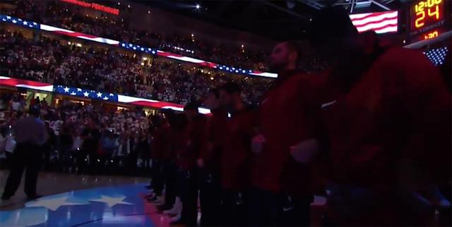 "Members of the <a class=""link rapid-noclick-resp"" href=""/nba/teams/cle/"" data-ylk=""slk:Cleveland Cavaliers"">Cleveland Cavaliers</a> stand and lock arms during the national anthem before their season opener against the <a class=""link rapid-noclick-resp"" href=""/nba/teams/bos/"" data-ylk=""slk:Boston Celtics"">Boston Celtics</a>. (Screencap via Sports Illustrated)"