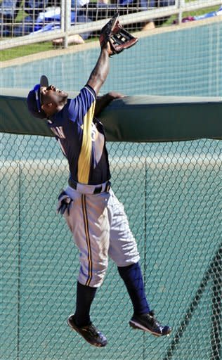 Milwaukee Brewers right fielder Nyjer Morgan climbs the fence but can't catch a two-run home run by Los Angeles Dodgers' Andre Ethier in the fifth inning of a spring training baseball game Tuesday, March 20, 2012, in Glendale, Ariz. (AP Photo/Mark Duncan)