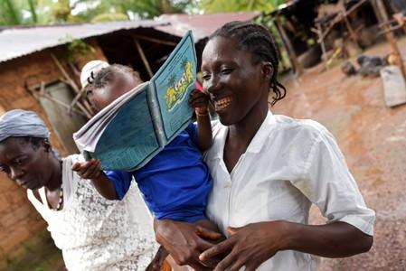 Mariatu Sesay, 15, smiles as she carries her daughter Nadia while she walks outside her house in the countryside village of Sierra