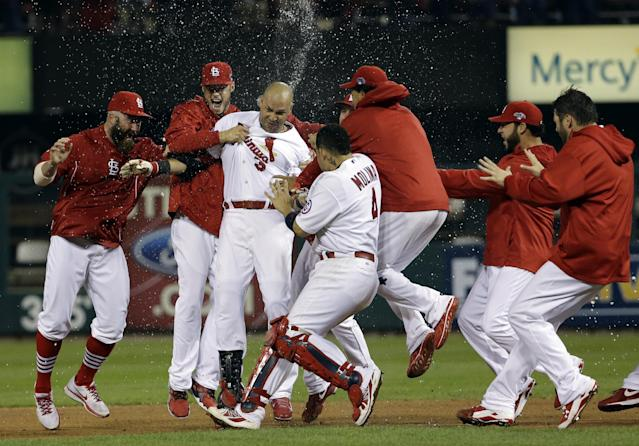St. Louis Cardinals' Carlos Beltran is congratulated by teammates after his game-winning hit during the 13th inning of Game 1 of the National League baseball championship series against the Los Angeles Dodgers Saturday, Oct. 12, 2013, in St. Louis. (AP Photo/David J. Phillip)