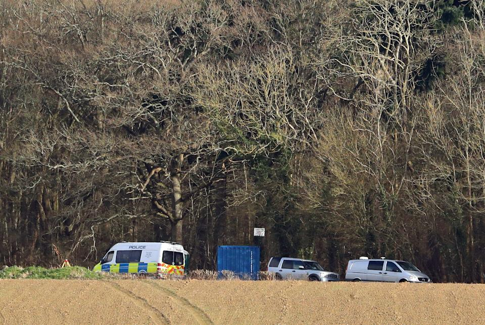 Police vehicles at the scene where human remains, that have been identified as that of 33-year-old Sarah Everard, were found hidden in woodland in Ashford, Kent. The Met Police announced on Wednesday that the diplomatic protection officer held over the disappearance of Sarah Everard has been arrested on suspicion of murder. Picture date: Friday March 12, 2021.