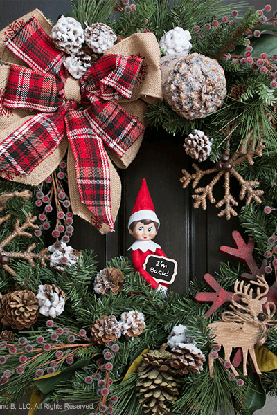 """<p>Make your gorgeous wreath the star of your Elf's return by inviting him to nestle into its branches. He's going to have to enter through the front door, anyway!</p><p><strong>Get the tutorial at <a href=""""https://www.elfontheshelf.com/blog/epic-elf-returns"""" rel=""""nofollow noopener"""" target=""""_blank"""" data-ylk=""""slk:Elf on the Shelf"""" class=""""link rapid-noclick-resp"""">Elf on the Shelf</a>.</strong> </p>"""