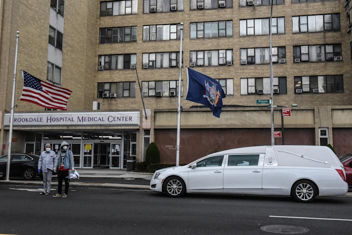 NEW YORK, NY - APRIL 27 : A white hearse stands outside the Brookdale Hospital Medical Center on April 27, 2020 in the Brooklyn borough in New York City. Although New York's daily coronavirus death toll has dropped to below 400, New York City remains the epicenter of the disease with over 12,000 deaths to date. (Photo by Stephanie Keith/Getty Images)