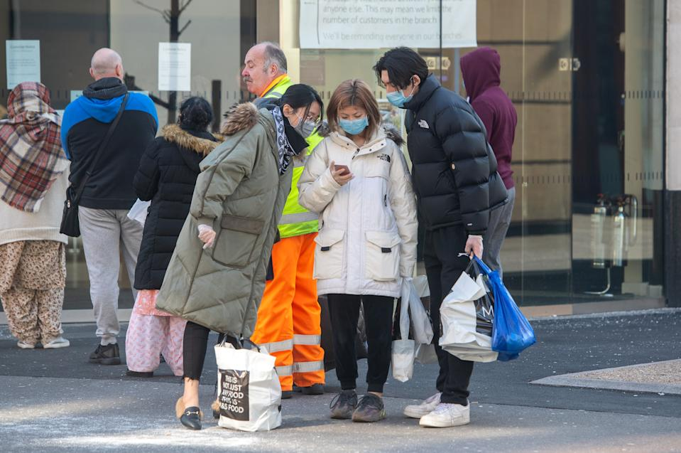 People wearing face masks look at a mobile phone in Leicester, the day after Prime Minister Boris Johnson put the UK in lockdown to help curb the spread of the coronavirus. (Photo by Joe Giddens/PA Images via Getty Images)