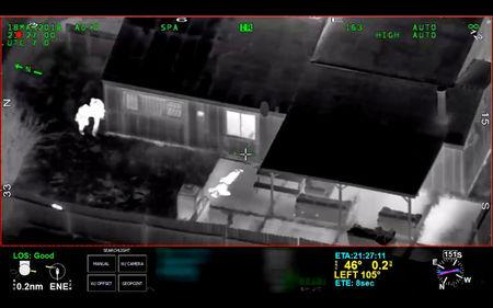 Stephon Clark, 22, is visible on the ground after two police officers (L) shot him, in this still image captured from police aerial video footage released by Sacramento Police Department, California, U.S., on March 21, 2018.   Courtesy Sacramento Police Department/Handout via REUTERS
