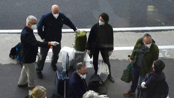 A photo of some of the global team of researchers wearing masks standing next to their luggage.